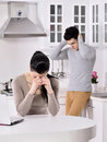 Unhappy couple in the kitchen offend home Stock Photography