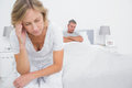 Unhappy couple sitting on opposite ends of bed after a fight in bedroom at home Stock Photography
