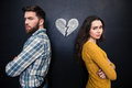 Unhappy couple standing over chalkboard background with drawn broken heart