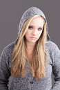 Unhappy face portrait of a caucasian girl with long blond hair wearing a hooded jersey and an expression on her Royalty Free Stock Image