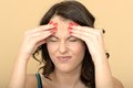 Unhappy fed up stressed young woman with a painful headache in agony dslr royalty free image scrunching her forehead both hands Stock Images