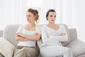 Unhappy friends not talking after argument on couch young female at home the Royalty Free Stock Image