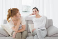 Unhappy friends not talking after argument on the couch young female at home Stock Image