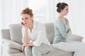 Unhappy friends not talking after argument on the couch young female at home Stock Photography