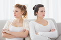 Unhappy friends not talking after argument on the couch young female at home Royalty Free Stock Images