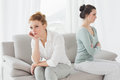 Unhappy friends not talking after argument on the couch young female at home Stock Photos