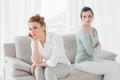 Unhappy friends not talking after argument on the couch young female at home Royalty Free Stock Photography