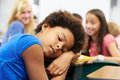 Unhappy girl being bullied in class leaning on desk upset Royalty Free Stock Photos