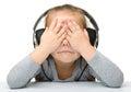 Unhappy girl listening music using headphones Stock Photography