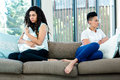Unhappy lesbian couple sitting on sofa