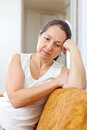 Unhappy mature woman on sofa at home Royalty Free Stock Photo