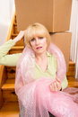 Unhappy mover woman pauses moving boxes up the stairs in a house Royalty Free Stock Image