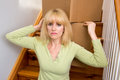 Unhappy mover woman pauses moving boxes up the stairs in a house Royalty Free Stock Photography