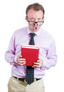 Unhappy negative looking teacher student library worker wearing glasses and holding books looking angry at you a close up portrait Royalty Free Stock Image