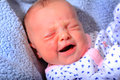 Unhappy newborn a close up of an baby laying on a blue blanket shallow depth of field Royalty Free Stock Images