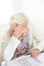 Unhappy senior woman looking at financial bill on the table Royalty Free Stock Photos