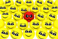 A unhappy smiley stands out from the crowd Stock Photo
