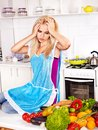 Unhappy tired woman at kitchen preparing food Stock Photo
