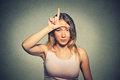 Unhappy woman giving loser sign on forehead, looking at you, disgust on face Royalty Free Stock Photo