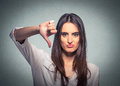 Unhappy woman giving thumb down gesture looking with negative expression