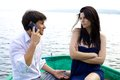 Unhappy woman looking boyfriend smiling on the phone jealous about talking and Royalty Free Stock Images