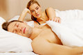 Unhappy woman lying in bed stressed when her husband sleeping women Stock Photo