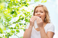 Unhappy woman with paper napkin sneezing people healthcare rhinitis and allergy concept over green natural background Stock Image