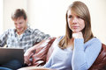 Unhappy woman sitting on sofa as partner uses laptop sits Stock Images
