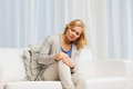 Unhappy woman suffering from pain in leg at home Royalty Free Stock Photo