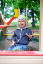 Unhappy Young boy playing in the sandbox Royalty Free Stock Photo