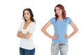 Unhappy young female friends not talking after argument over white background Royalty Free Stock Photography