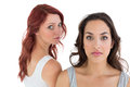 Unhappy young female friends not talking after argument over white background Royalty Free Stock Photos