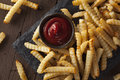 Unhealthy baked crinkle french fries with ketchup Stock Photography