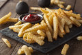 Unhealthy baked crinkle french fries with ketchup Stock Images