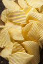 Unhealthy crinkle cut potato chips ready to eat Stock Photos