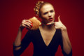 Unhealthy eating junk food concept guilty pleasure woman with burger portrait of a fashionable model holding and pointing on it Stock Photo