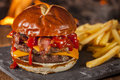 Unhealthy homemade barbecue bacon cheeseburger with fries Royalty Free Stock Photo