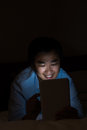 Unhealthy using tablet behavior one asian man bright digital device in the dark room Stock Photography