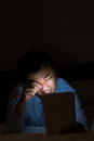 Unhealthy using tablet behavior one asian man bright digital device in the dark room Stock Image