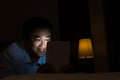 Unhealthy using tablet behavior one asian man bright digital device in the dark room Royalty Free Stock Photo