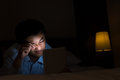 Unhealthy using tablet behavior one asian man bright digital device in the dark room Stock Images