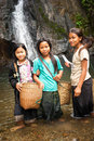Unidentified cute asian girls near tropical waterfall laos vang vieng dec with baskets washing vegetables in rain forest river Royalty Free Stock Photography