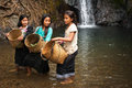 Unidentified cute asian girls near tropical waterfall laos vang vieng dec with baskets washing vegetables in rain forest river Royalty Free Stock Photos