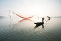 Unidentified fisherman checks his nets in early morning on river in hoian vietnam is recognized as a world heritage site by Stock Photos
