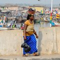 Unidentified Ghanaian woman carries a baby and a basin on the r Royalty Free Stock Photo