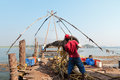Unidentified indian fishermen descend their chinese fishing net into the sea fort kochi india jan in beach of fort kochi Stock Photo