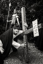 Unidentified man portraying Jesus Christ carries large wooden cross during reenactment of the Crucifixion. Black and White Royalty Free Stock Photo