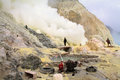 Unidentified miners harvest raw sulphur from the crater of Kawah Ijen volcano Royalty Free Stock Photo
