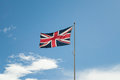 Union jack flying blu sky as background Stock Photos