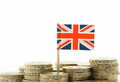 Union jack and money a miniature the flag of great britain stands behind stacks of british pound coins on a white background with Royalty Free Stock Photos